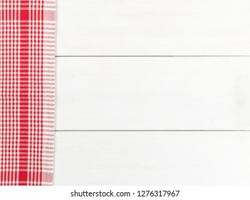 Red checkered dishcloth on white wooden plank table flat lay top view from above with copy space