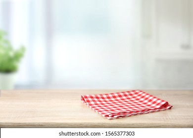 Red checkered folded picnic cloth on wooden table empty space background.Towel over the plank blurred kitchen background.