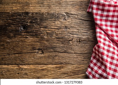Red checkered kitchen tablecloth on rustic wooden table.