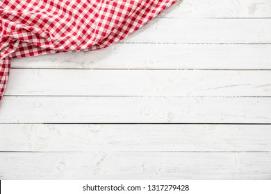 Red checkered kitchen tablecloth on wooden table.