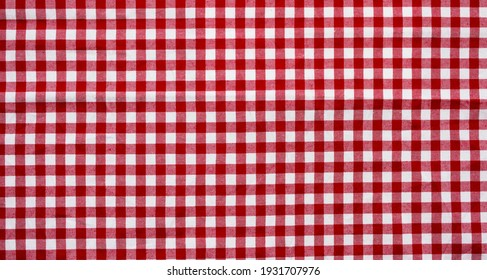 Red checkered tablecloth background. Textiles, fabric.