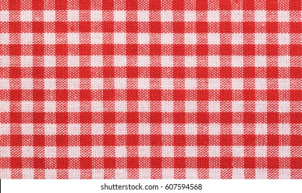 Red checkered tablecloth fabric background texture, close-up.