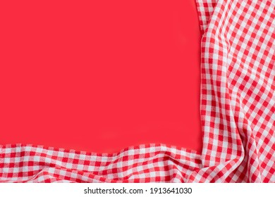 Red checkered tablecloth on a red background. Top view with copy space