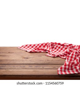 Red checkered tablecloth on empty wooden table. Napkin close up top view mock up for design. Kitchen rustic background.