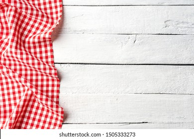 Red checkered tablecloth on white wooden table. Top view