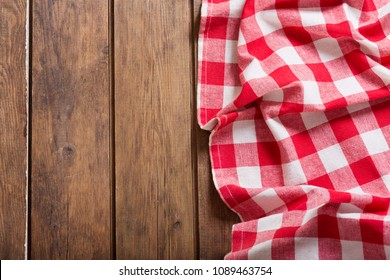 red checkered tablecloth on wooden table, top view