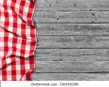 Red checkered tablecloth on wooden background