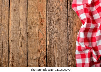 Red checkered tablecloth right frame on vintage wooden table background - view from above