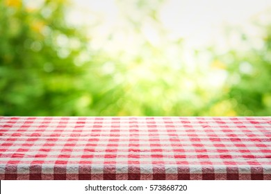 Red checkered tablecloth texture top view with abstract green bokeh from garden in morning background.For montage product display or design key visual layout.