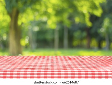 Red checkered tablecloth texture top view with abstract green bokeh from garden in morning background.For montage product display or design key visual layout and summer season.