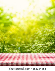 Red checkered tablecloth texture top view with abstract green bokeh from garden in morning background.picnic concept
