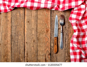 Red checkered tablecloth top and right frame, knife and fork on vintage wooden table background - view from above