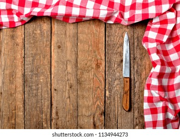 Red checkered tablecloth top and right frame and knife on vintage wooden table background - view from above