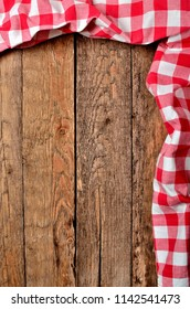 Red checkered tablecloth top and right frame on vintage wooden table background - view from above - vertical photo