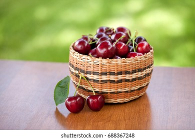 Red cherries in basket on wooden table