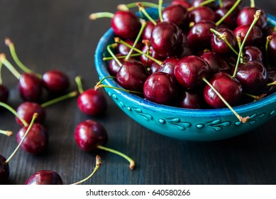 red cherries in green ceramic bowl on dark background