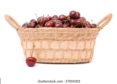 Red cherries in wooden basket isolated on white
