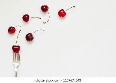 Red cherry fruits and fork on white background with copy space for text. Summer, diet, healthy food eating consept. Top view, flat lay, layout, pattern