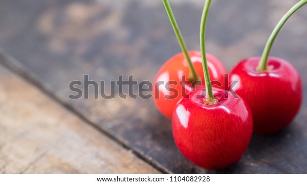Red cherry fruits on wooden table top