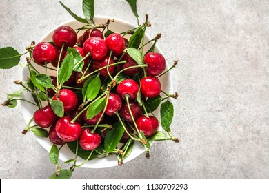 Red cherry on plate on white background, sweet cherries, top view