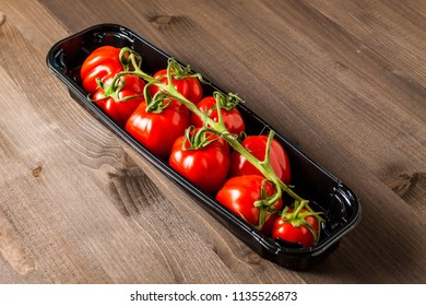 Red cherry tomatoes in a box isolated on wooden background