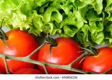 Red cherry tomatoes on branch and lettuce leaves.