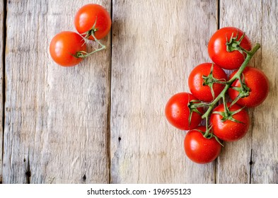 red cherry tomatoes on a white wood background. toning. selective focus on the right tomato