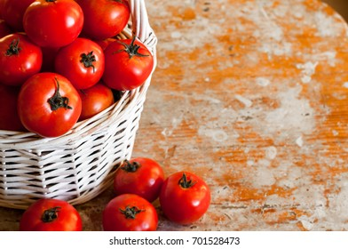 Red cherry tomatoes in a woven basket on a white background on wooden table