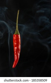 Red chili on a black background with smoke