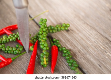 red chili pepper and green peppercorns on wood background with knife with copy space, spicy healthy herbal ingredient of Thai food.
