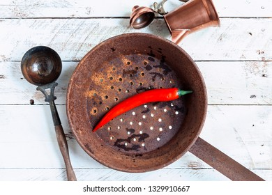 red chili pepper inside a rusty old style pot on a vintage white planks table