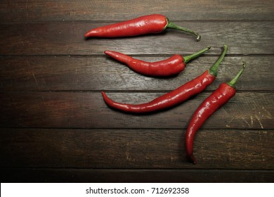 Red chili pepper isolated on a wooden background. Food concept.