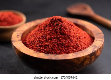 Red chili powder or paprika in a wooden bowl on a dark background, close-up. Cooking ingredients, flavor.
