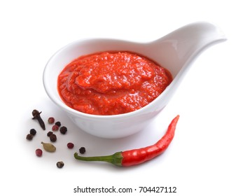 Red chili sauce in the sauce boat. With pepper. Isolated on white background.