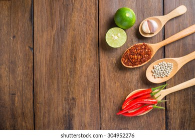 Red chilli, garlic and lemon on wood texture background