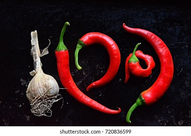 red chilli and garlic on a black background