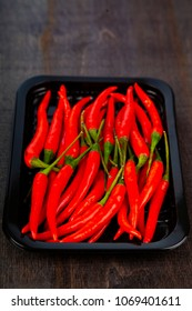 Red chilli pepper is a dark background. Chili in the tray.