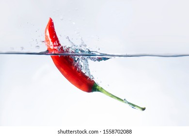 Red chilli pepper falling  water splashes White background