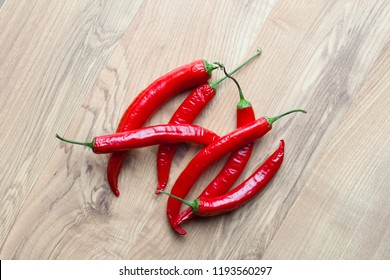 Red chilli peppers on wooden background