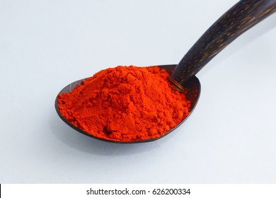 Red Chilli Powder in scoop over white background