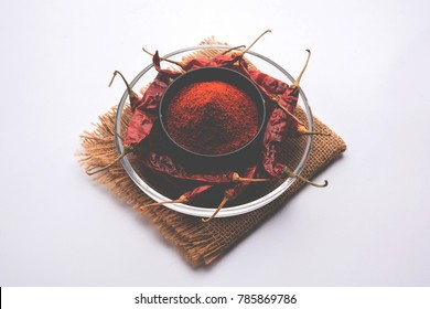 Red Chilly Powder heap in a bowl with dried Mirchi over white background , Selective focus