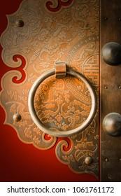 Red Chinese door with gold metal pattern art carving and door clasp on the door in Beijing, China