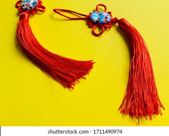 Red Chinese knots for good luck on yellow background with copy space.