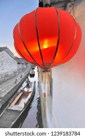 Red Chinese Lantern alongside a canal with boats in Zhou Zhuang, China