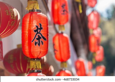 Red chinese lanterns in an old village with the character for tea outside on a sunny day