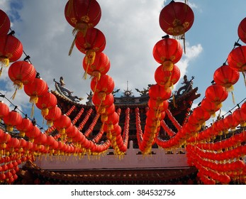red chinese traditional lanterns hanging across in rows against blue clear sky