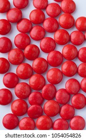 Red chocolate candies. Close up top view, white background. Red color.