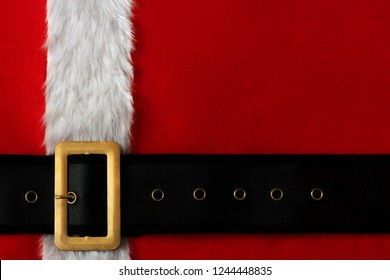 Red Christmas background of Santa suit with belt and gold buckle.