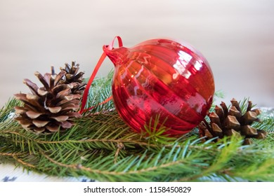Red Christmas ball with pine cons on blurred branch of Christmas tree on white background