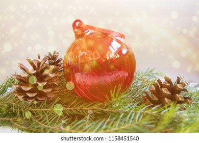 Red Christmas ball with pine cons on branch of Christmas tree on white background  with lights